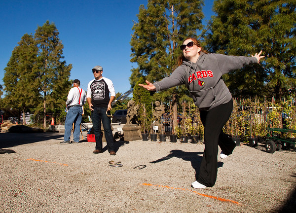 Alani and Adam Frederick, Clarksville, play a game of horseshoes during the Walnut Ridge Nursery & Garden Center's 100th birthday party at their location along Hamburg Pike in Jeffersonville on Saturday morning. The center had refreshments and several games for attendants to enjoy, as well as taking 19.13 percent off their merchandise in remembrance of their opening in 1913. Staff photo by Christopher Fryer