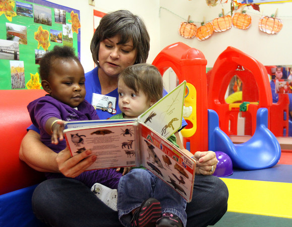 Clark Memorial Hospital employee Karen Alexander reads to Chance Smith, left, and Laila Capehart Wednesday morning a the Goodwill BridgePointe Children's Learning Center. More than 100 Clark Memorial workers fanned out across Clark and Floyd counties to provide community service. Staff photo by C.E. Branham