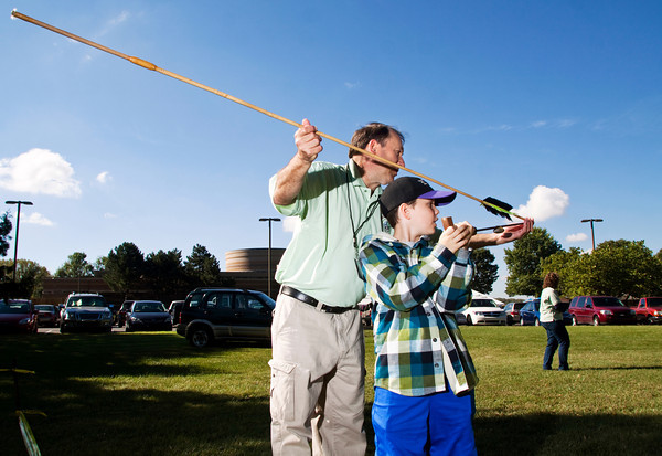Volunteer Gary Potter, Louisville, helps Conner Paris, 9, Floyds Knobs, load an atlatl with a dart at the games and atlatls station during the annual Archaeology Day at Falls of the Ohio State Park in Clarksville on Saturday morning. Staff photo by Christopher Fryer