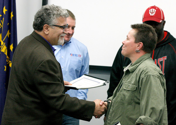 Victor Burgos, Manufacturing Skill Standards Council instructor for Ivy Tech, hands a certificate to Terri Kidd who graduated from WorkOne Southern Indiana's Production Technician program. Local businesses sent their employees to the course to help them move into leadership roles. Staff photo by Jerod Clapp