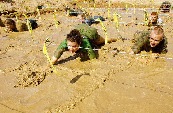 Racers crawl underneath barbed wire as they negotiate the final obstacle of the Muddy Fanatic 5K Adventure Race at the former Glenwood Training Center in Sellersburg on Saturday morning. Over 2000 participants negotiated over 30 obstacles on a 3.1 mile course either as individual racers or as part of a team. Staff photo by Christopher Fryer