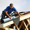 Anthony Nasby works on the roof of the Habitat for Humanity home being built for his family on Twin Oaks Drive in Henryville. Staff photo by C.E. Branham