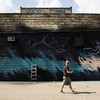 Garrett Parks, Louisville, takes a step back to survey his work on a graffiti production near the flood wall in New Albany on Wednesday afternoon. Parks and several other artists will be working to complete the abstract piece over the next few days. Staff photo by Christopher Fryer