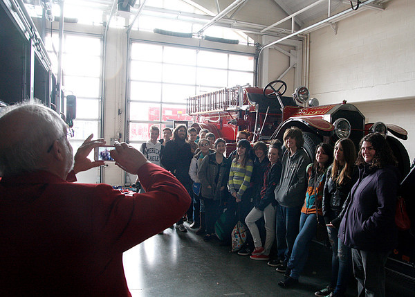 Curt Peters, chairman of the Vintage Fire Museum board, photographs a class from Community Montessori in front of a famous New Albany fire engine from 1937. The class spent Friday visiting several places downtown to learn about some of the city's history and their role in its future. Staff photo by Jerod Clapp