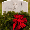 A wreath rests against a head stone after a wreath laying ceremony at the New Albany National Cemetery on Saturday afternoon. Members of the Indiana Wing Civil Air Patrol's Falcon Composite Squadron held a ceremony and placed more than 750 wreaths around the cemetery to honor veterans for the holiday season as part of Wreaths Across America. Staff photo by Christopher Fryer