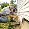 Project manager and lead carpenter Garry Teigland, of Edwardsville, works on the siding during the Floyd Action Network sponsored restoration process of Emery's Ice Cream Parlor at the Urban Fusion Community Garden in New Albany on Saturday morning. The structure is owned by the Floyd County Historical Society and was moved to its current location by Indiana Landmarks last year. Staff photo by Christopher Fryer