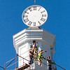 A crew with DM Masonry works to place one of the four restored clock faces back on the clock tower of the Second Baptist Church in downtown New Albany on Tuesday morning. Staff photo by Christopher Fryer
