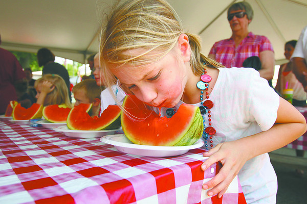 Veronica Sellers digs in as a competitor in the Charlestown Founder's Day watermelon eating contest Saturday afternoon. Staff photo by C.E. Branham
