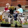 Janet Ayres. left, and Ann Merriman of Grinny Possum Fiber Arts sit near a parking space on Spring St. that was transformed into a park Friday. Several downtown businesses participated in the event called Parking Day. The event held in cities around the globe allows artists, activists and citizens to temporarily transform metered parking spaces into public parks and other social spaces. Staff photo by C.E. Branham