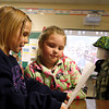 Nevaeh Adkins, a third-grader at Mount Tabor Elementary School, reads the description of robot to Elle Schweitzer, a second-grader for the school's Robot Museum. Adkins' robot, Captain George Freedom, is a medic who can run up to 70 mph and is also a decorated soldier. Staff photo by Jerod Clapp