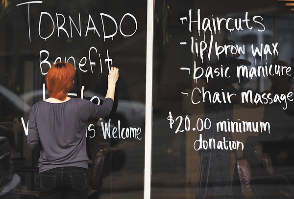 Springs Salon and Spa receptionist Natalie Carden paints a sign on the salon window promoting their benefit Monday. The Jeffersonville salon is donating 100 percent of the proceeds to tornado victims. Staff photo by C.E. Branham