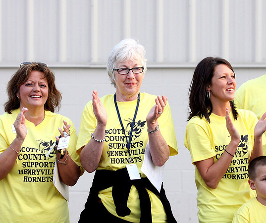Scott County educators, volunteers, and former educators applaud Henryville High School and Middle School students at they arrive for classes Monday morning at Mid-America Science Park in Scottsburg. Staff photo by C.E. Branham