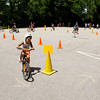Participants make their way through the bicycle safety rodeo course at the Griffin Center on Friday afternoon in New Albany. About 20 participants from the Riverside, Parkview and Griffin Street recreation centers learned about traffic rules and general bicycle safety in the Kosair Children's Hospital event through the New Albany Department of Parks and Recreation. Staff photo by Christopher Fryer