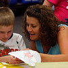 Zachary Nolan, a six-year-old first grader at S. Ellen Jones Elementary School, cuts out a raccoon he colored with the help of his teacher, Lori Savage. Students in the New Albany-Floyd County Consolidated School Corp. started their school year Monday. Staff photo by Jerod Clapp