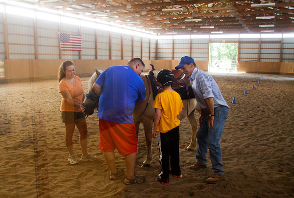 Bradford Woods counselor Anna Buchheit, left, volunteer David Newman, center left, and Horseshoes of Hope executive director John Lambert, right, assist Camp Riley camper Blake Duvall, 12, center right, in the indoor arena of Horseshoes of Hope Equine Academy at Bradford Woods near Martinsville on Tuesday morning. Staff photo by Christopher Fryer