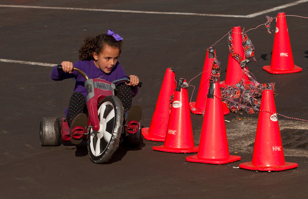 Carly Fonda, 5, of Floyds Knobs, comes around a turn during the Big Wheel race next to the Harvest Homecoming Stage along State Street in downtown New Albany on Saturday morning. Staff photo by Christopher Fryer