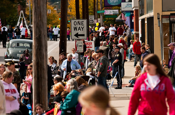Parade goers look on in downtown New Albany as the Harvest Homecoming Parade moves down Spring Street on Saturday afternoon. Staff photo by Christopher Fryer