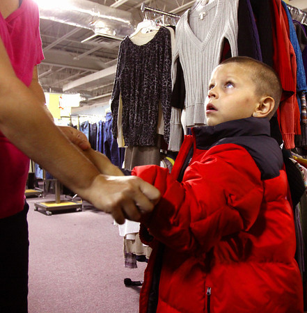 Aden Proctor looks up at his mother Shannon Best as she fits him for a coat at the Salvation Army Thrift Store clothes giveaway Wednesday. Staff photo by C.E. Branham