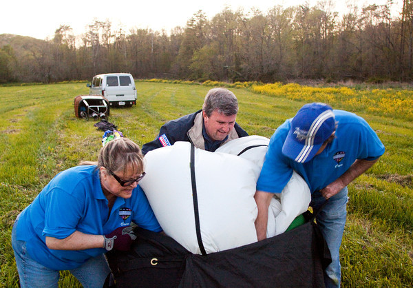 Balloon pilot Jerry Copas, center, and his chase crew, Pat Brown, left, and Brett Stoy, work to pack away a hot air balloon after a flight across part of southern Indiana on Monday evening. Copas will be competing in the Kentucky Derby Festival Great Balloon Race this week. Staff photo by Christopher Fryer