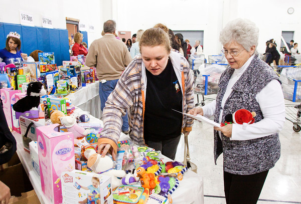 Volunteer Alice Glover, right, of Louisville, helps Angel Tree recipient Amber Jenkins, of Jeffersonville, pick out toys for her two children at the Salvation Army in New Albany on Saturday afternoon. Staff photo by Christopher Fryer