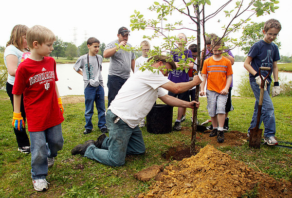 Arborist Greg Mills, of New Albany, helps students from Mt. Tabor Elementary School plant a tree in observance of Earth Week at Sam Peden Community Park on Wednesday afternoon. Staff photo by Christopher Fryer.