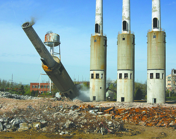 A smoke stack tumbles down Thursday morning at the River Ridge Commerce Center. Three more smoke stacks and a water tower were also taken down Thursday. Staff photo by C.E. Branham