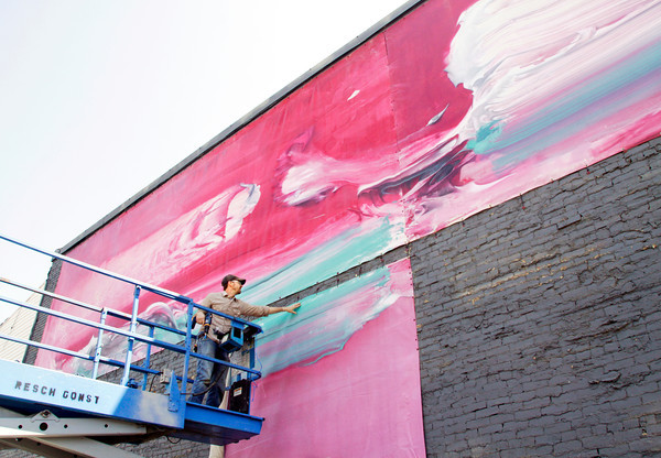 "Dan Phalzgraf, of Louisville, the installation liaison for the New Albany Public Art Project, works from a lift while installing part of ""Painting"" by Boris Zakic, of Georgetown, Ky., in downtown New Albany on Tuesday morning. Zakic's piece represents the visual art and artists historic theme for the project, and is one of four installations going up this year. Staff photo by Christopher Fryer"