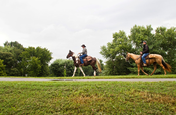 Richard Mills, left, riding Willy, a Tennessee walking horse, and Ryan Rollins, riding Blondie, a palomino, head west along the flood wall near the Falls of the Ohio in Clarksville on Saturday morning. Saturday's ride was the first leg of a 3-4 month journey for Mills to raise awareness and funds for neglected and abused horses. He plans to ride about 25 miles a day until he reaches Great Falls, Mont., while following the route that Lewis and Clark used for their exploration of the West in the 19th century. Staff photo by Christopher Fryer