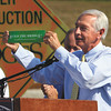Kentucky Gov. Steve Beshear holds up a 1990's bumper sticker while delivering his remarks at the East End Bridge Crossing groundbreaking Thursday in Jeffersonville. Staff photo by C.E. Branham