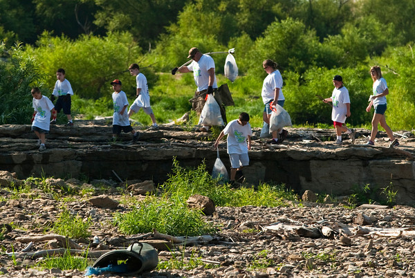 Volunteers from Cub Scout Pack 10, out of Clarksville, move up the river bank with items they collected during the annual Clark County Ohio River Sweep at the Falls of the Ohio State Park on Saturday morning. Staff photo by Christopher Fryer