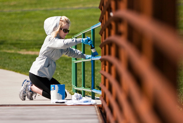 Floyd County Parks and Recreation board member Leslie Lewis-Sheets paints a hand rail while volunteering during the cleanup day at Sam Peden Community Park in New Albany on Saturday morning. Staff photo by Christopher Fryer