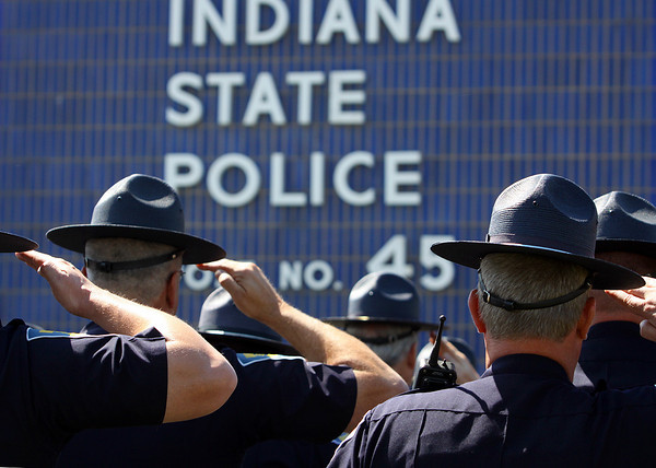 Indiana State Troopers stand at attention as Taps is played at the conclusion of the Sellersburg District's memorial service Wednesday. Staff photo by C.E. Branham