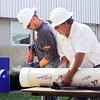 Duke Energy employees Billy McClelland, left, of Charlestown, and Rex Cochran, of New Albany, open a 25-year-old time capsule during a ceremony at the company's Clarksville location on Wednesday morning. This year also marks the company's 100th anniversary. Staff photo by Christopher Fryer