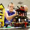 Fourth grader Tyler Barrett, 10, of Greenville, puts the finishing touches on his Lego creation Crazy But Peaceful Town before presenting in the Basic Craft category of the Floyd County 4-H Fair during preliminary, open judging in Newlin Hall at the fair grounds in New Albany on Thursday afternoon. Open judging was started last year so participants would have the opportunity to explain their projects to the judges to increase the educational value of the contest process. Staff photo by Christopher Fryer