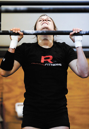 Rachel Kellington, of Louisville, does a pull-up during a CrossFit competition at Clark Floyd CrossFit in New Albany on Saturday morning. Kellington placed first in the women's competition and Charlie Sims, of Louisville, placed first in the men's. The owner of the facility, Case Belcher, graduated from Henryville High School in 2005 and held the event to raise tornado relief funds for the school's athletic department. Staff photo by Christopher Fryer