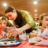 Jill Abetti, of New Albany, helps her daughters Hazel, left, and Elizah as they taste ingredients during a ginger bread house workshop in the auditorium at the New Albany-Floyd County Public Library on Saturday morning in downtown New Albany. The Abetti family are regular patrons of the library and this is their second year to attend the annual event. Library staff and volunteers helped more than 60 other participants create houses with milk cartons, graham crackers and countless sweets during the morning session. Staff photo by Christopher Fryer