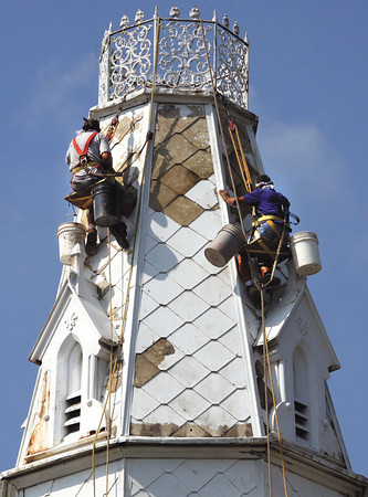 Workers with D M Masonry, suspended in a bosun's chair, begin restoration work on the steeple of First Presbyterian Church in Jeffersonville. The complete project, involving a three-color paint scheme to bring out architectural detail, should be completed in 4-6 weeks according to Pastor Don Summerfield. Staff photo by C.E. Branham