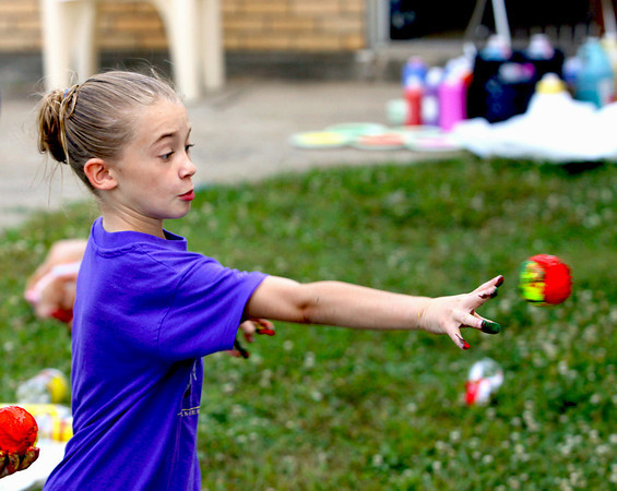 Emily James hurls a paint covered tennis ball at a piece of paper at the New Albany-Floyd County Department of Parks and Recreation Messy Kids Art Camp. The event was held at the Griffin Street Recreation Center on Monday. Staff photo by C.E. Branham