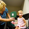 Pam Russ, of Louisville, holds a mirror up for Anna Hornung, 3, of New Albany, so she can approve her face painting during the Cancer Survivor's Reunion Carnival at the Cancer Center of Indiana in New Albany on Friday afternoon. Staff photo by Christopher Fryer