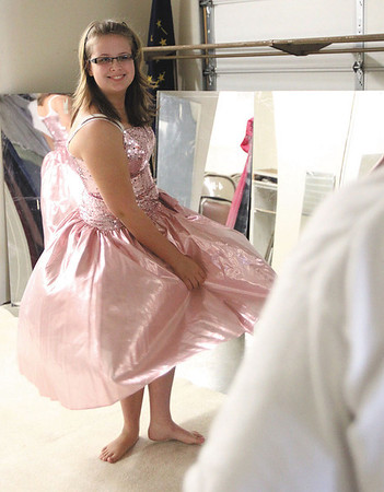 Abby Carlisle models a dress for her parents at Prom Aid on Sunday. Staff photo by C.E. Branham