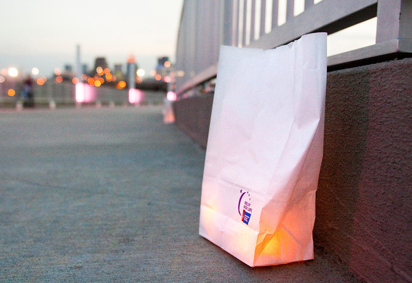A luminaria bag sits illuminated at dusk along the ramp to the Big Four Bridge in Louisville during the American Cancer Society's Every Candle Has a Name luminaria event on Thursday evening. About 5,000 bags were illuminated as part of the ceremony in honor of those affected by cancer and in commemoration of the society's 100th birthday. Staff photo by Christopher Fryer