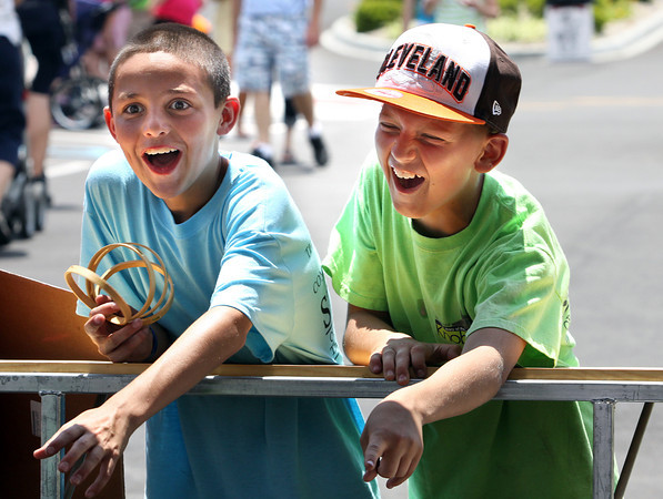 Landon Sprigler, left, and friend Andrew Donovan react after Donovan won a ring toss game at KnobsFest on Saturday afternoon. The annual event is held on the grounds of St. Mary of the Knobs Catholic Church. Staff photo by C.E. Branham
