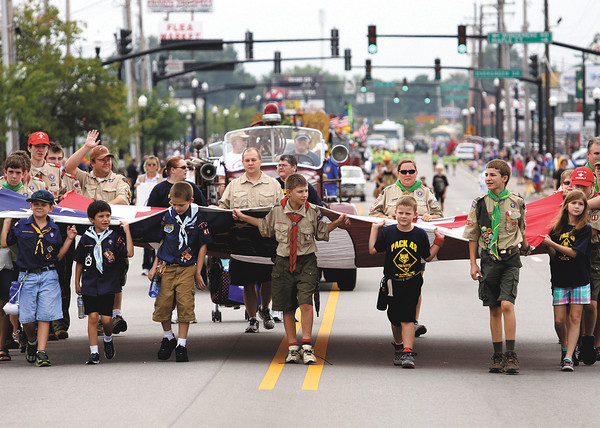 Local Boy Scouts and Cub Scouts carry the American flag down Eastern Boulevard Monday in the Clarksville Parade. Staff photo by C.E. Branham