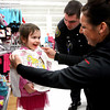 Four-year-old Marissa Kern enjoys shopping for clothes with New Albany police officer Patrick Clarke and his wife Kirsten Clarke Tuesday evening at Meijer in New Albany. Meijer and the New Albany Police Department teamed up to give 70 local children $250 worth of clothes and toys. Staff photo by C.E. Branham