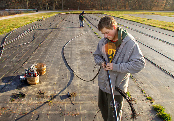 H.B. Farms laborers Josh Jackson, right, of Clarksville, and Daniel Ramirez, of Sellersburg, work on replacing irrigation hoses for a mum plot at the corner of Scottsville and Starlight roads in Floyd County on Wednesday afternoon. Staff photo by Christopher Fryer