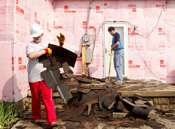 Volunteers Mady Ford, 12, left, and her brother Joseph, 18, both of Henning, Illinois, clean up shingles as they are removed from the roof of a home on South Front Street in Henryville on Wednesday morning. The home was damaged during the March 2 tornadoes and the siblings came down on their spring break with their parents to work with a group of volunteers from their father's employer, Flex N Gate, located in Urbana, Illinois. Staff photo by Christopher Fryer