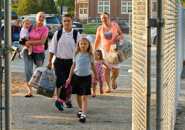 The Fiorello and Brady families head into St. Mary's Catholic Academy for the first day of classes on Tuesday morning in New Albany. The school currently has more than 130 students enrolled for classes ranging from pre-school to the eighth grade. Staff photo by Christopher Fryer