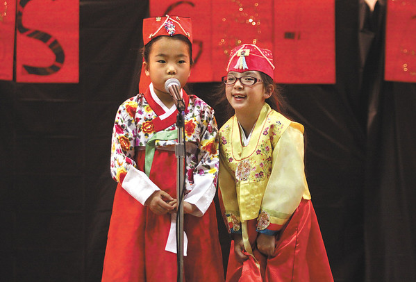 Wilson Elementary School first-graders Martha Chang, left, and Jane Mi Han Masek spoke Korean salutations with English translations at the Jeffersonville school's talent show Tuesday night.  Staff photo by C.E. Branham