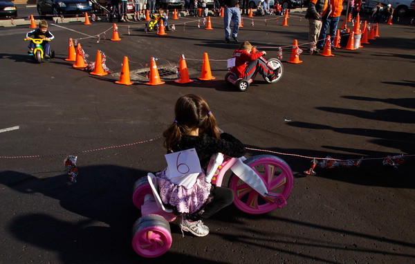 Jaila Kenney, 6, of Georgetown, watches the competition as she waits to participate in the Big Wheel race next to the Harvest Homecoming Stage along State Street in downtown New Albany on Saturday morning. Staff photo by Christopher Fryer