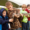 From left, Jackson Smith, 5, of New Albany, and Kameron Holliday, 9, of Charlestown, take care of the tail-end of an 11-foot Burmese python during a Silly Safari show at the 2013 Mother Earth Celebration next to the New Albany Riverfront Amphitheater on Saturday afternoon. Staff photo by Christopher Fryer
